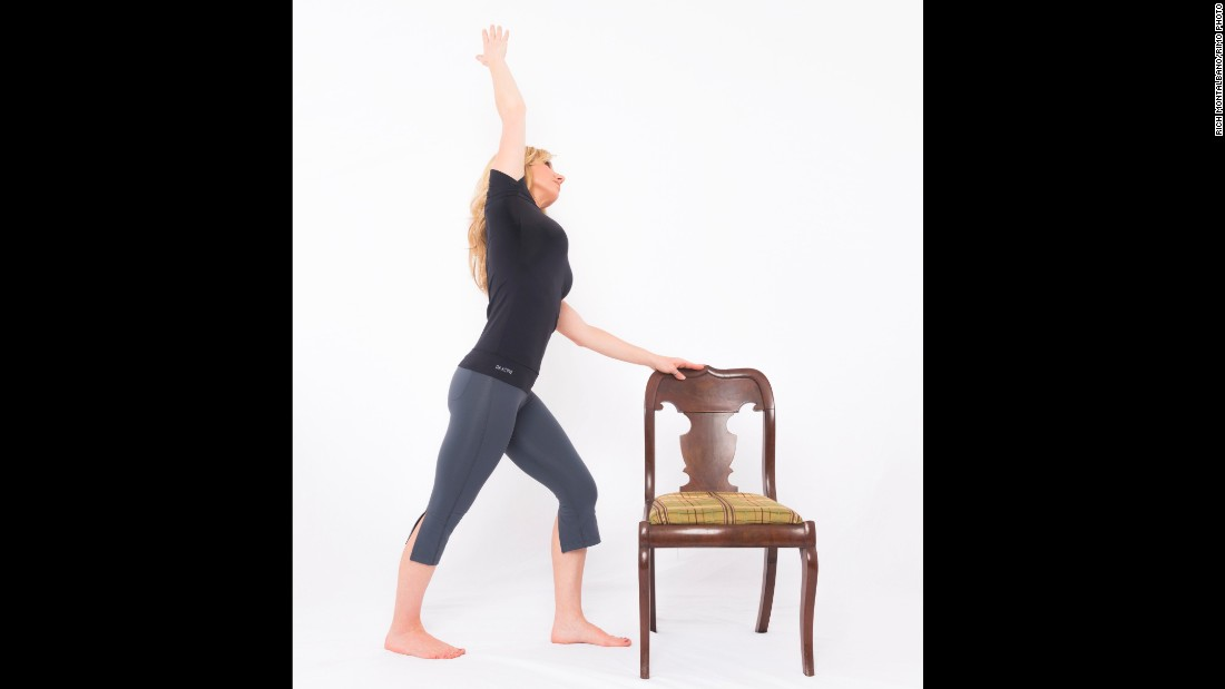Place your left hand lightly on top of your chair or desk, step your right foot back into a short lunge. Drop your back heel and point your toes out slightly. Bend your front knee to align above your ankle, keeping your back leg straight. Inhale as you lift your right arm up and over your head. Exhale as you side bend to the left. Keep your core activated for balance and avoid arching your lower back. Press the front of your right hip forward to release your right hip flexors. Hold for three long, deep breaths. Repeat on the other side.