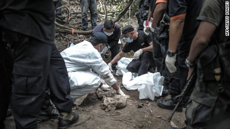 Forensic teams exhume graves found at trafficking camps