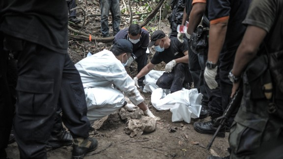 A Royal Malaysian Police forensic team handles exhumed human remains in a jungle at Bukit Wang Burma in the Malaysian northern state of Perlis, which borders Thailand, on May 26, 2015. Malaysian police May 26 began the grisly job of exhuming dozens of graves found in a series of remote human-trafficking camps along the Thai border in the latest grim turn in the region