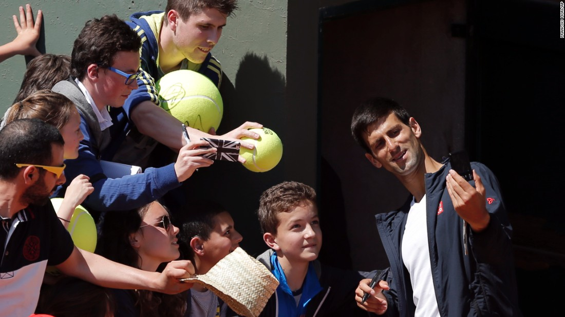 The world's top-ranked tennis player, Novak Djokovic, takes a photo with fans in Paris after a French Open training session on Saturday, May 23.