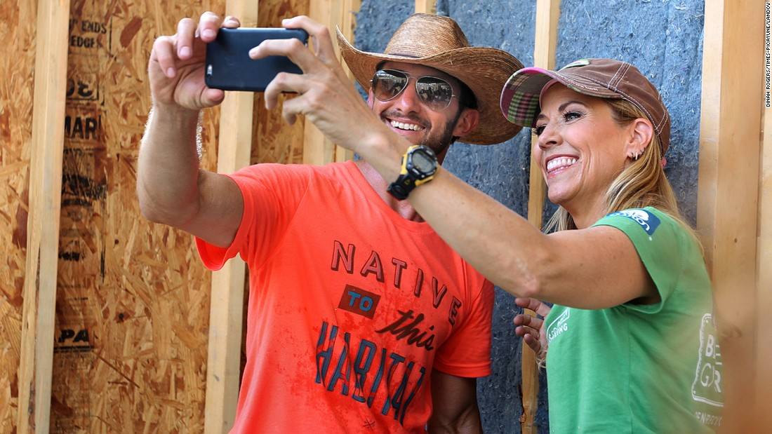 "Singer Sheryl Crow holds the phone with Billy Puckett, a Habitat for Humanity ""house leader,"" as hundreds of volunteers worked to build houses in New Orleans on Thursday, May 21."