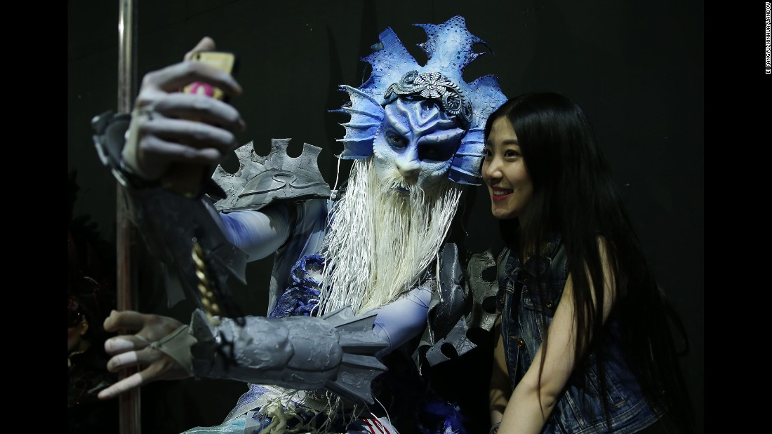 A costumed character takes a selfie with a spectator after a design competition in Beijing on Sunday, May 24.