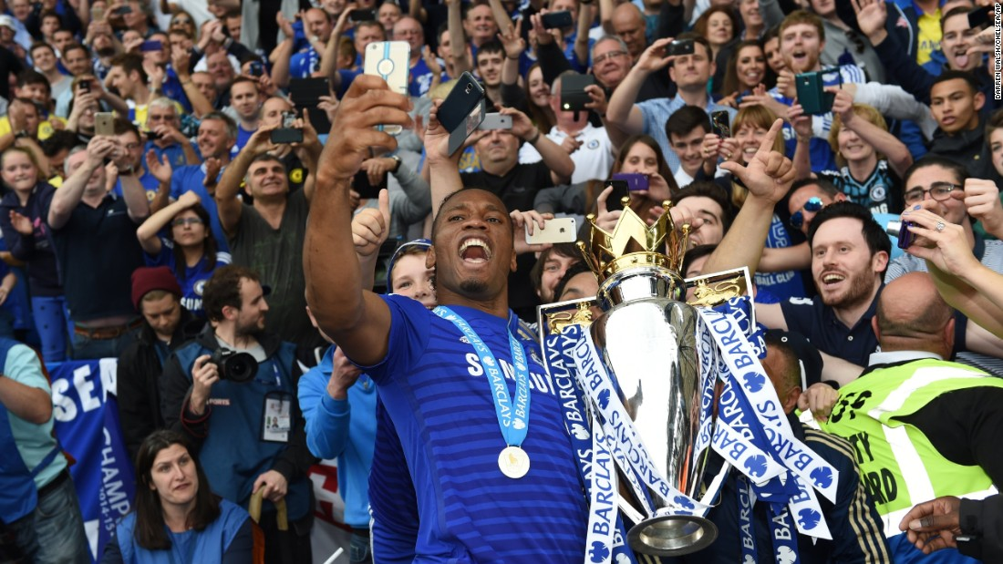 Chelsea striker Didier Drogba takes a selfie with the Premier League Trophy after a soccer match in London on Sunday, May 24.