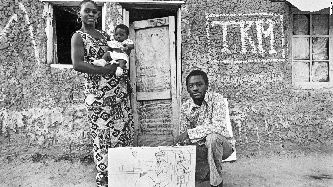 Kanda-Matulu with his family. Here he's holding the unfinished painting of 'Declaration d'Indépendance'.