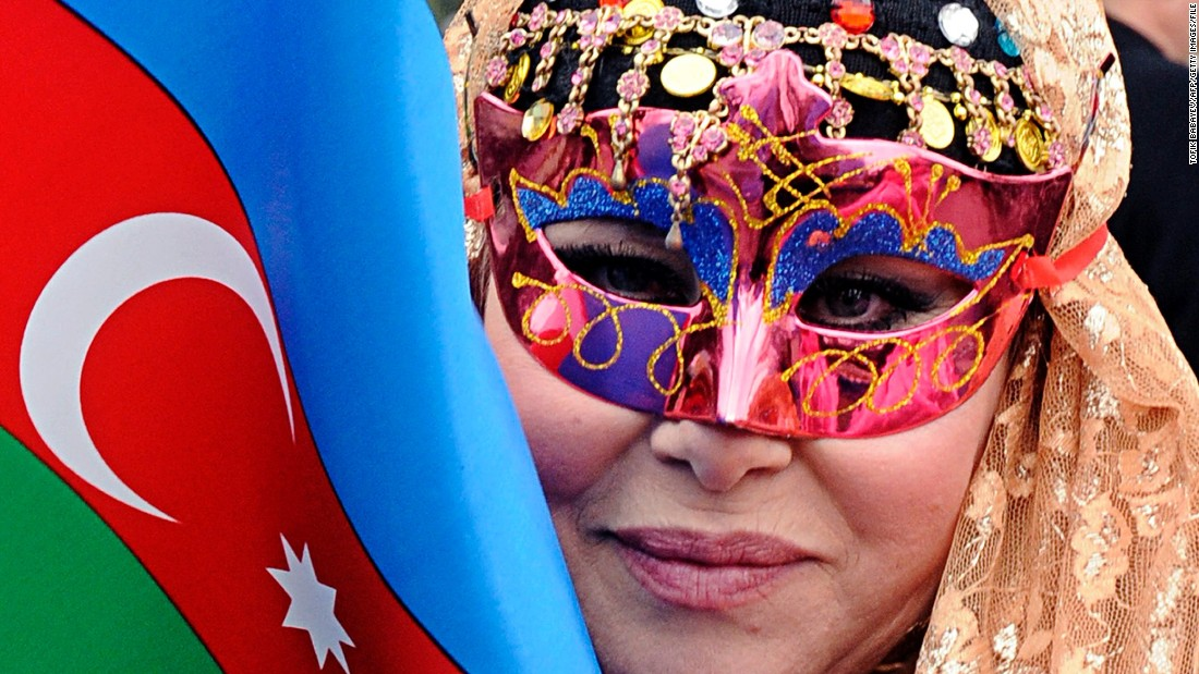 A masked woman holds an Azerbaijani flag during a spring welcome festival in Baku.
