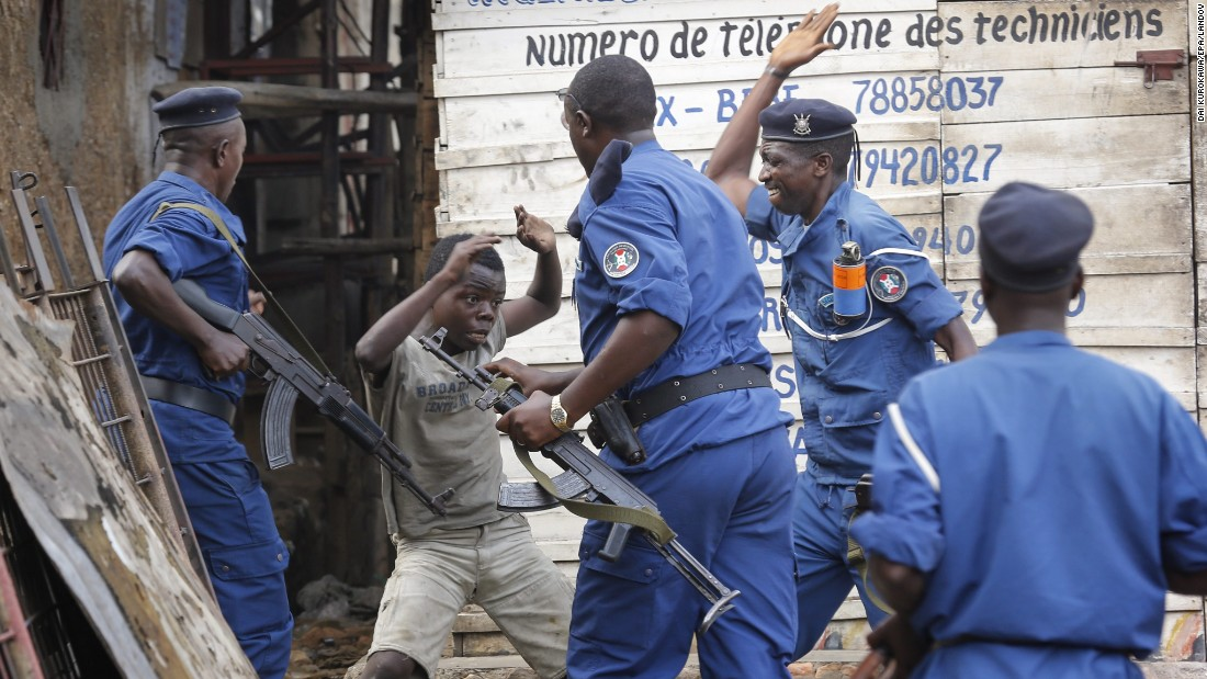 A young Burundian boy tries to cover himself as police officers beat him at an anti-government demonstration in Bujumbura on Tuesday, May 26.