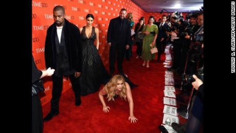 Amy Schumer pretends to trip and fall on the floor in front of Kim Kardashian and Kanye West at the Time 100 Gala.