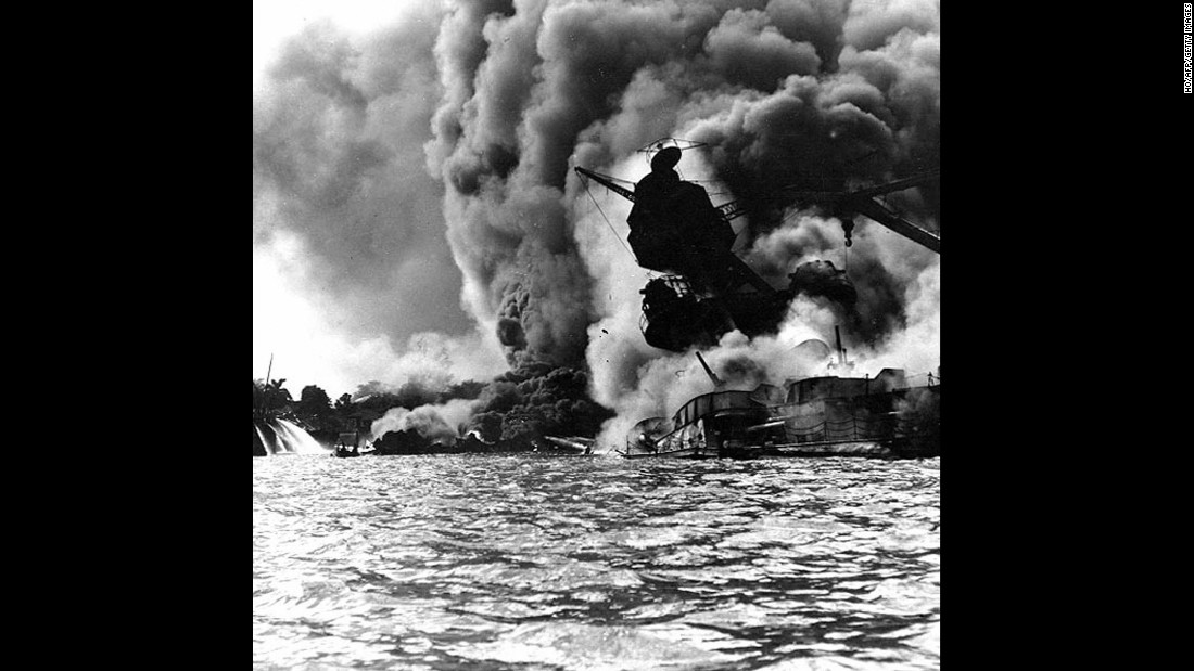 The USS Arizona burns furiously on December 7, 1941. The ship's forward magazines exploded when a Japanese bomb hit it. The remains of many of the 1,177 U.S. military personnel who died aboard the Arizona are still inside the wreck.