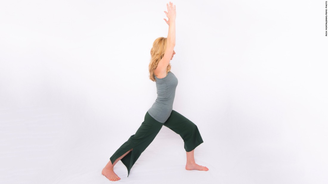 Santas demonstrates Warrior One, a basic standing yoga pose that lengthens the upper body while stretching hip flexors and stabilizing the low back. From standing, step back into a lunge but drop your back heel and point your toes out 45 degrees. Keep your back leg straight with your forward knee flexed above your ankle. Lift your arms overhead, shoulder-distance apart. Hold for three to five long, deep breaths. Repeat on the other side.