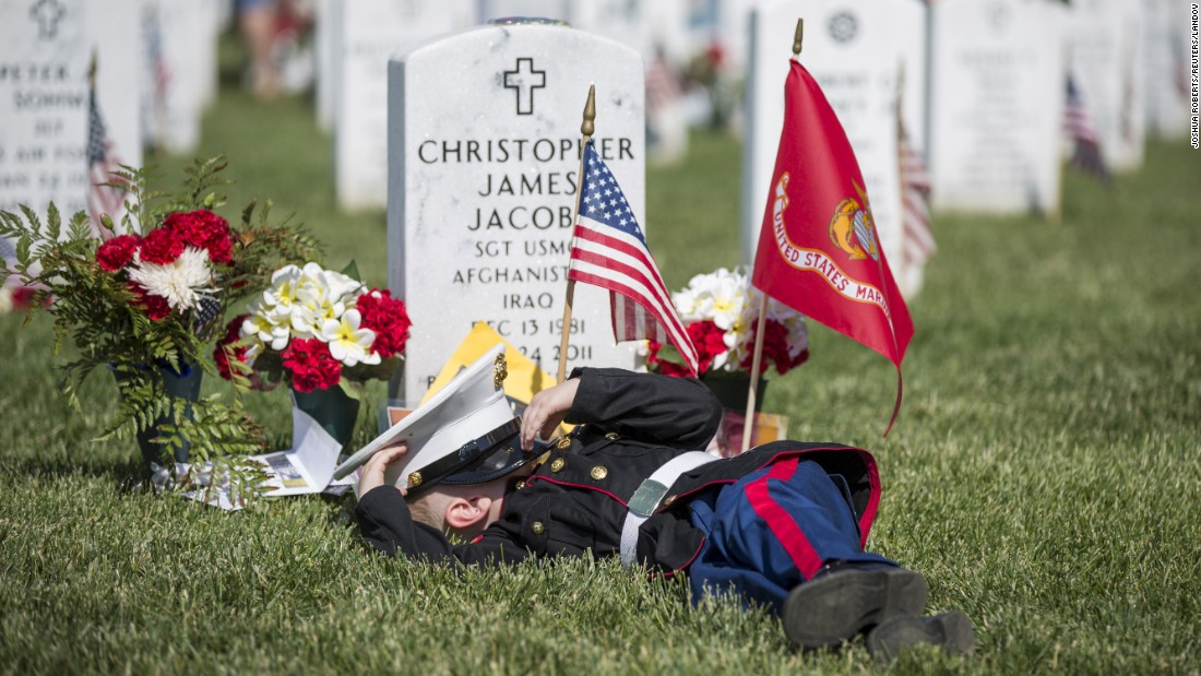 "Christian Jacobs, 4, lies on the grave of his father, Christopher James Jacobs, during a <a href=""http://www.cnn.com/2015/05/23/us/gallery/memorial-day-2015/index.html"" target=""_blank"">Memorial Day</a> event Monday, May 25, at Arlington National Cemetery in Virginia."