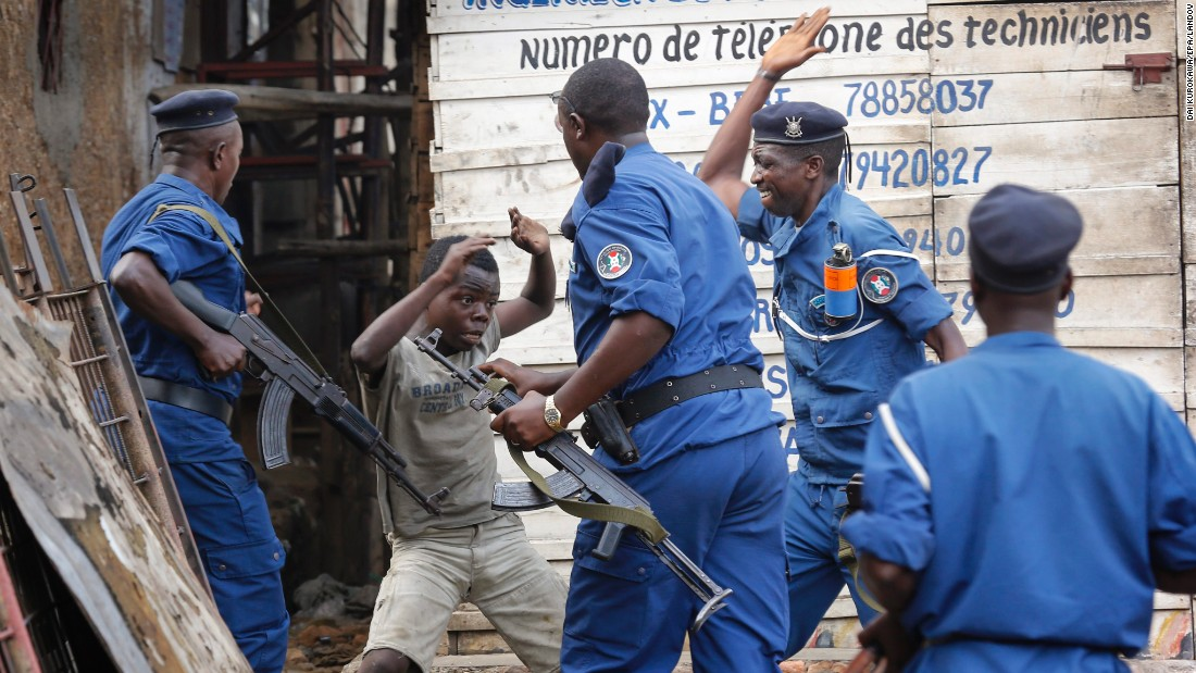 "A young boy tries to cover himself as police officers beat him at an anti-government demonstration in Bujumbura, Burundi, on Tuesday, May 26. Police fired shots to disperse people <a href=""http://www.cnn.com/2015/05/14/world/gallery/burundi-unrest/index.html"" target=""_blank"">protesting against President Pierre Nkurunziza</a> and his bid for a third term."