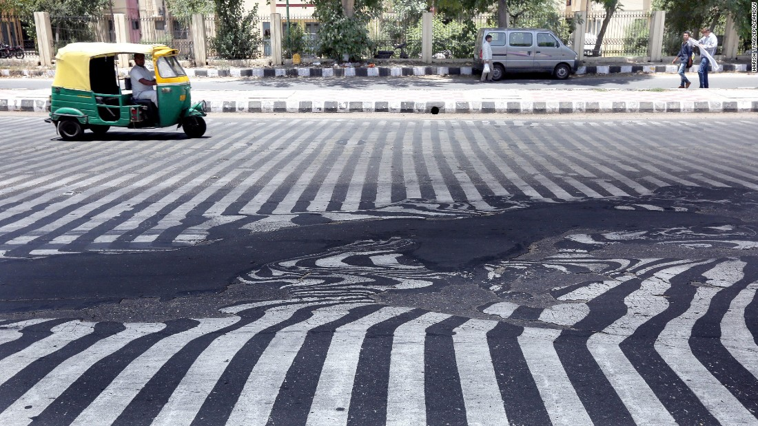 "Road markings appear distorted as asphalt starts to melt because of the high temperature in New Delhi on Wednesday, May 27. <a href=""http://www.cnn.com/2015/05/26/world/gallery/india-deadly-heat-wave/index.html"" target=""_blank"">A blistering heat wave</a> has killed more than 1,300 people in India."