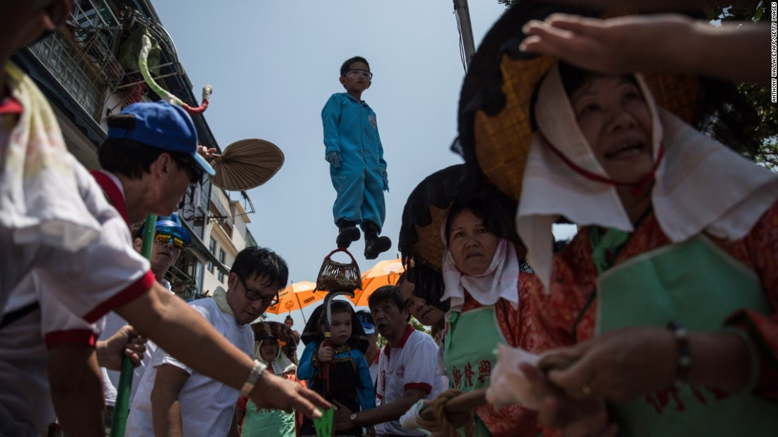 A young boy dressed as a deity is paraded on a float during the Bun Festival in Hong Kong on Monday, May 25. The Bun Festival is held every year to placate the hungry ghosts of old pirates.