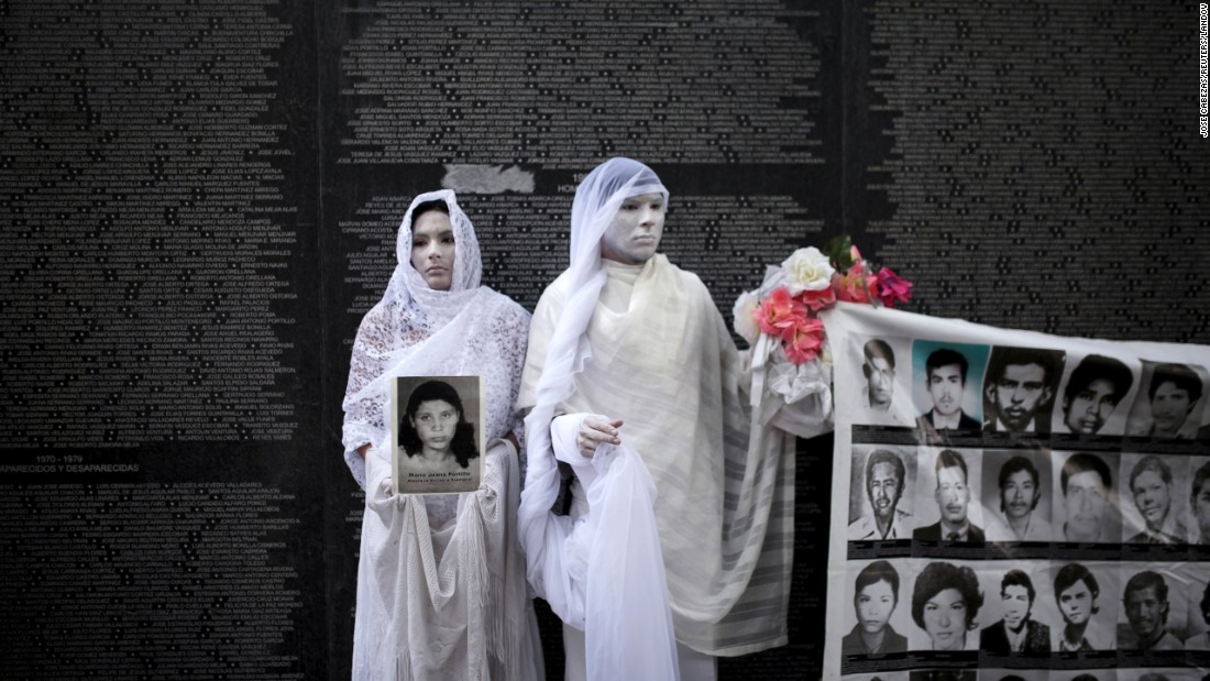 Performers in San Salvador, El Salvador, stand in front of a monument Tuesday, May 26, for people who disappeared during the Salvadoran Civil War. The 12-year war ended in 1992.