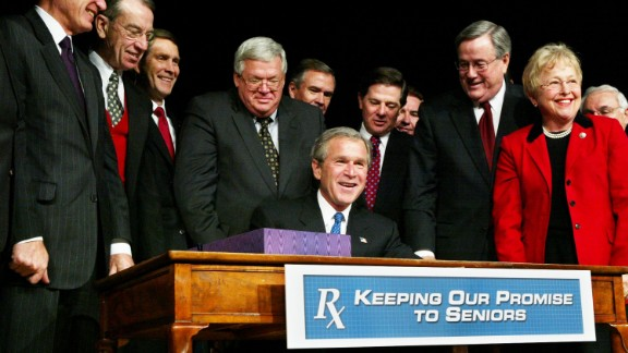 Hastert stands behind President George W. Bush as he signs Medicare legislation in December 2003. Hastert fought hard for the bill in the House, leading to a three-hour vote on November 22, 2003.