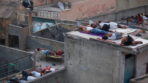 People sleep on roofs in New Delhi on May 29, to escape the heat trapped in their concrete homes on. A blistering heat wave has killed more than 1,300 people in the country.