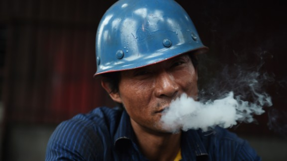 This photo taken on May 28, 2015 shows a worker smoking during a break at a demolition site in Beijing.