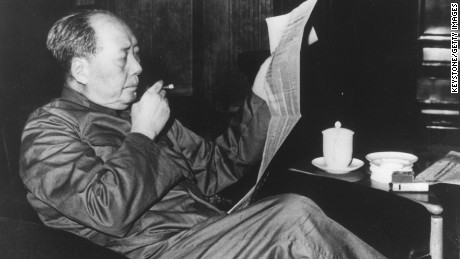 Mao Zedong (1893-1976), Chinese Communist leader, reading a newspaper and smoking a cigar.