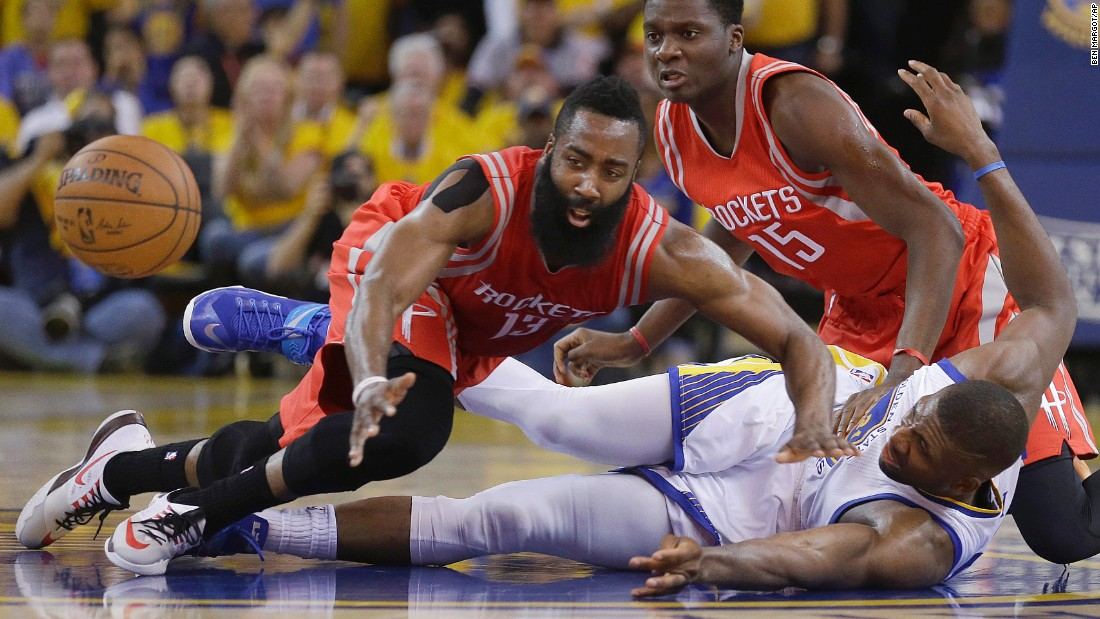 Houston's James Harden, left, reaches for a loose ball over Golden State's Festus Ezeli on Wednesday, May 27. Golden State won the game 104-90, clinching a spot in the NBA Finals.