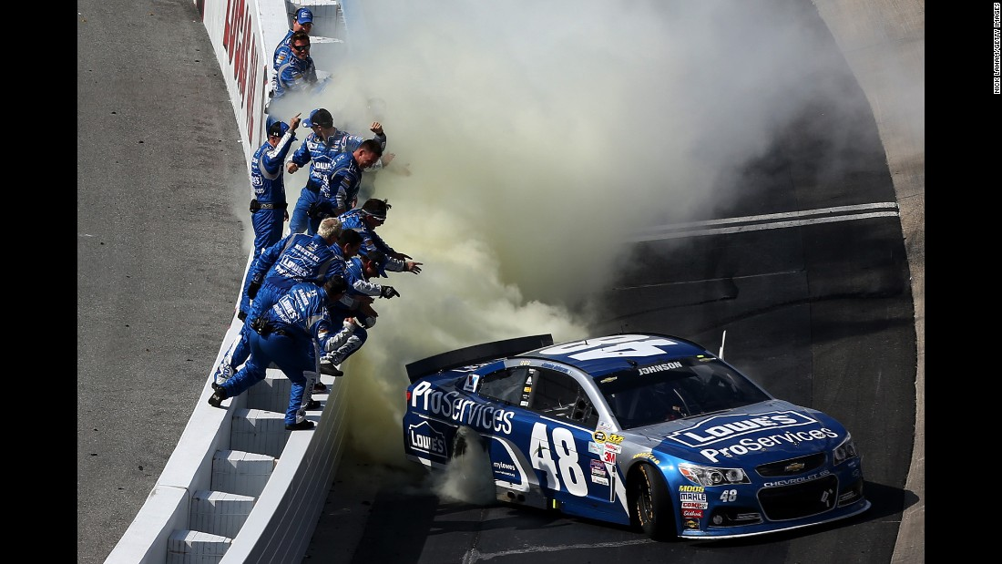 NASCAR driver Jimmie Johnson is cheered by his team while he celebrates his Sprint Cup victory in Dover, Delaware, on Sunday, May 31. It was his fourth win of the season.