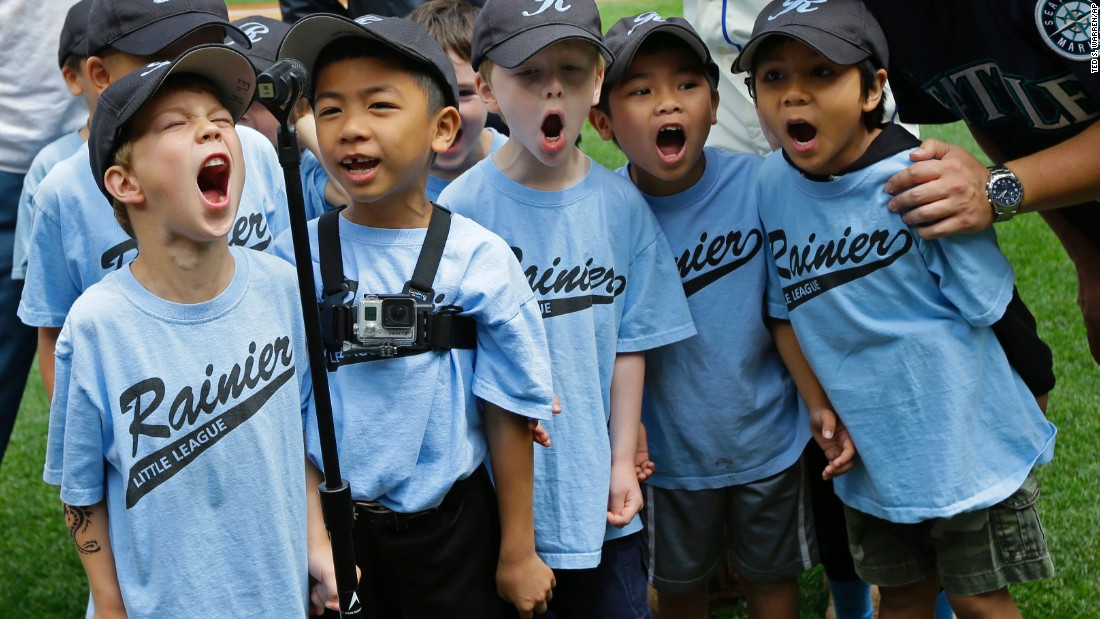 "Players from the Blue Rockets, a Little League team from Rainier, Washington, yell ""Play ball!"" before the start of a Major League Baseball game in Seattle on Sunday, May 31."