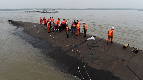 Rescuers work at the site of the overturned passenger ship on China
