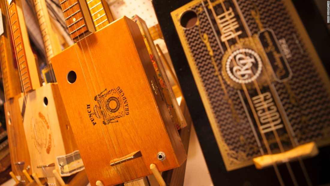 CNN's Mike Rowe gets a lesson in music history by learning how to make a guitar out of a cigar box. Pictured here are three- and four-string cigar box guitars built by Mike Snowden.