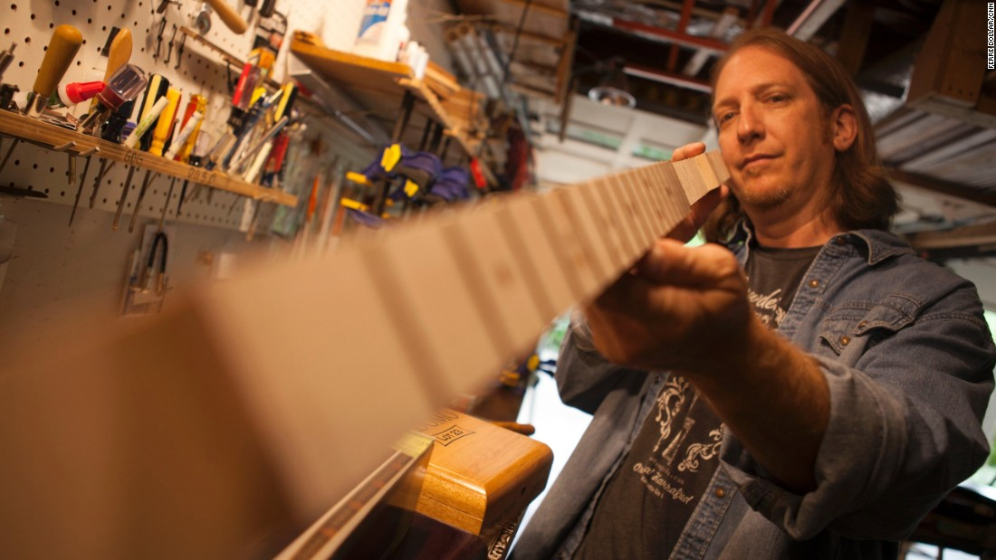 After fretting the cigar box guitar neck, Snowden holds it up to make sure the frets are even and the neck is straight.