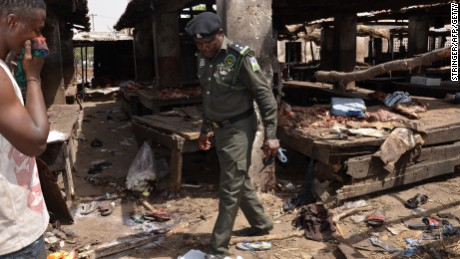 A Nigerian policeman inspects the site of a suicide attack at a busy cattle market in the northeastern Nigerian city of Maiduguri on June 2, 2015.