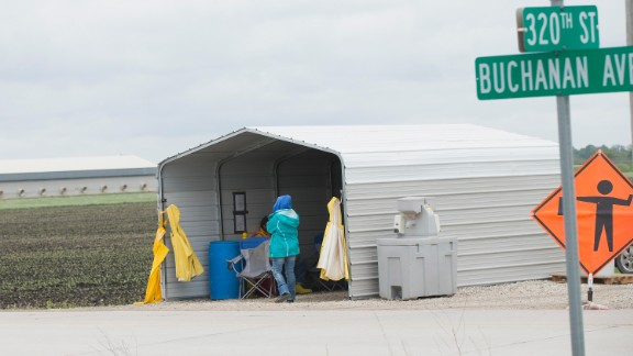 Workers at a checkpoint stand at an Iowa commercial poultry facility, reported to have been hit with a deadly strain of avian influenza which has forced poultry producers to kill off millions of birds in an attempt to stop the spread of the illness.