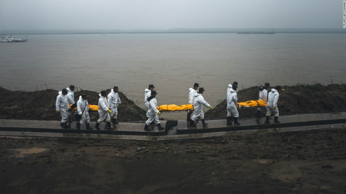 Rescue personnel carry the bodies of victims away from the banks of the Yangtze River in Jianli County, China, on Wednesday, June 3.
