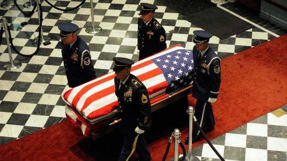 An honor guard carries Biden
