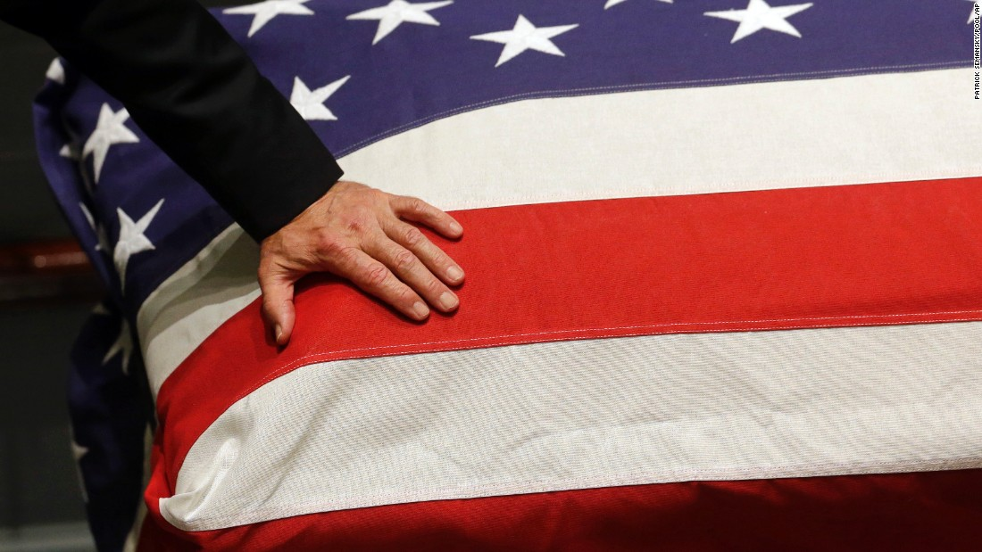 Biden rests his hand on the flag-draped casket.