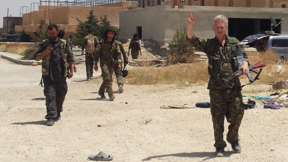 Enright, right, wears the military uniform of Kurdish fighters and flashes a victory sign last month in Syria.