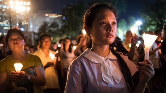 A student raises a candle at a vigil in Hong Kong on Thursday, June 4, 2015. Tens of thousands of people attended the service in remembrance of the 1989 Tiananmen Square protests. The vigil is held annually at Victoria Park, but this year's gathering took on greater meaning after last year's pro-democracy protests.