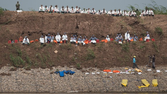 Rescue personnel rest next to empty stretchers on the riverbank on June 5.