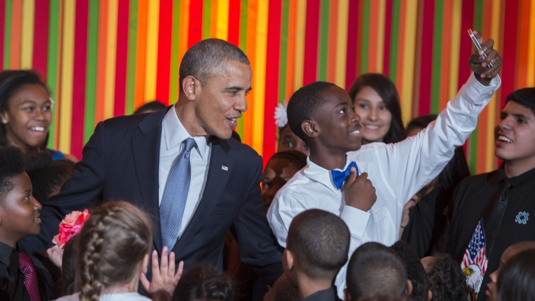 A student takes a selfie as Obama makes a surprise visit to the White House Talent Show in May 2014.