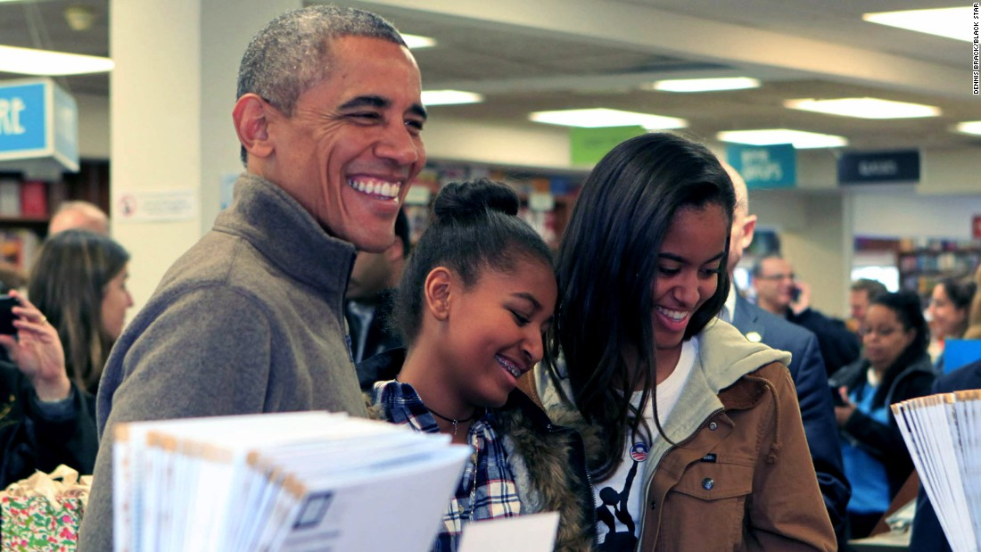 Obama buys books with his own kids, Sasha, center, and Malia, at Politics and Prose bookstore in Washington in November.