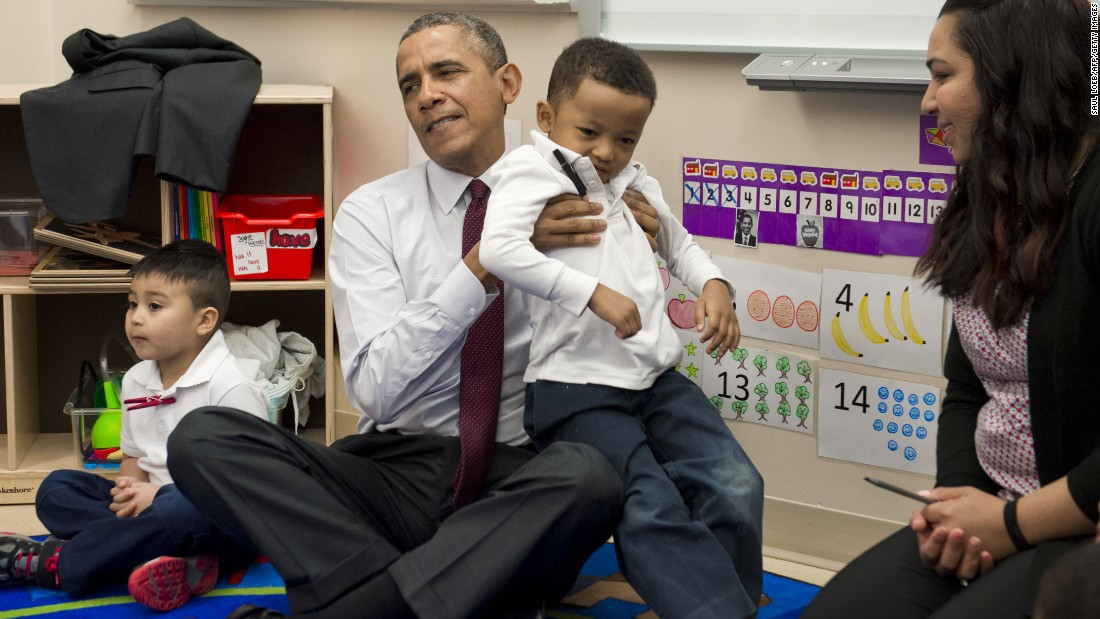 Obama puts student Marcus Wesby in his lap as he sits with children during a tour of a pre-K classroom at Powell Elementary School in Washington in March 2014.