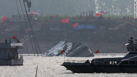 Marine boats patrol as a capsized ship is righted by cranes on the Yangtze River in Jianli county of southern China's Hubei province, as seen from across the river from Huarong county of southern China's Hunan province, Friday, June 5, 2015. The boat had been righted and teams would still try to lift the vessel even though the water inside it was weighing it down. Transport Ministry spokesman Xu Chengguang said earlier that the operation would involve divers putting steel bars underneath the ship, which would then be lifted by two 500-ton cranes. (AP Photo/Andy Wong)