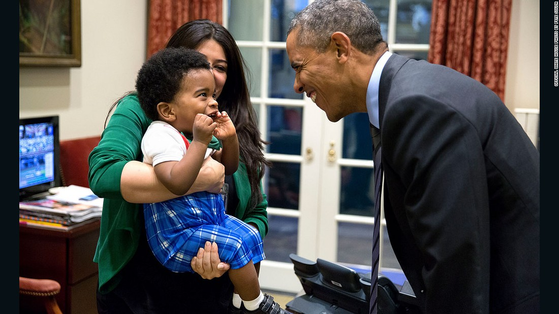 Obama greets a little boy held by Ferial Govashiri, personal aide to the president, in October.