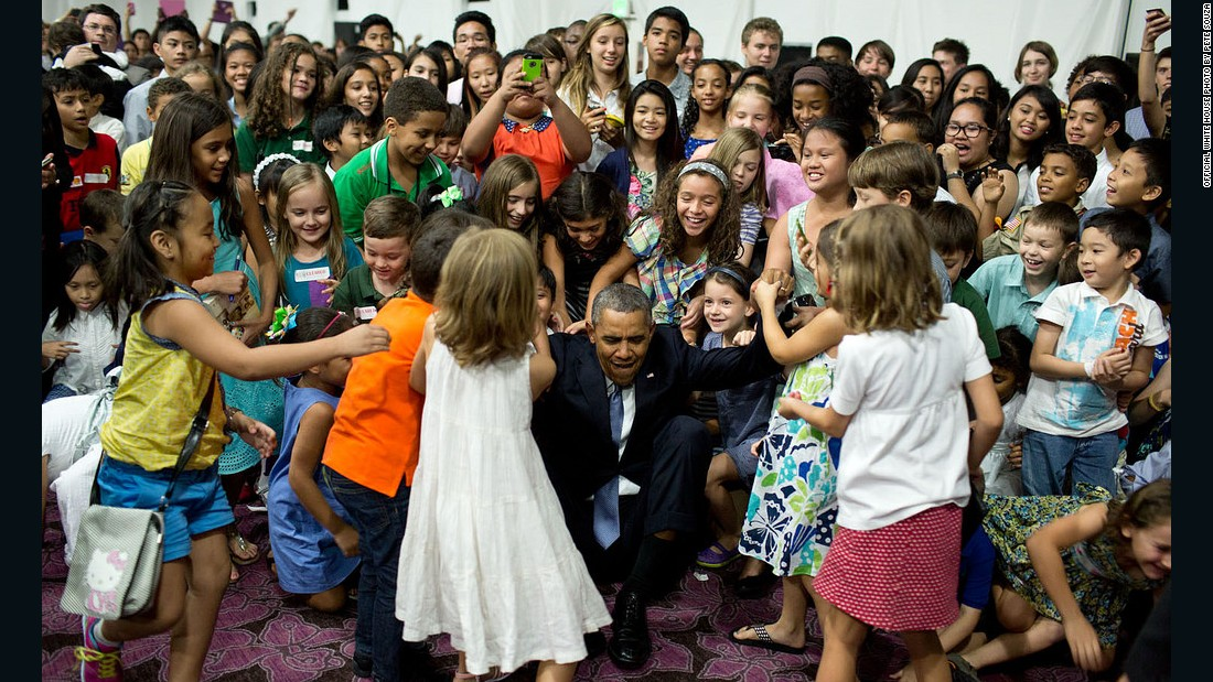 Obama beckons for help to get up after posing for a photograph with children at the U.S. Embassy in Manila, Philippines.
