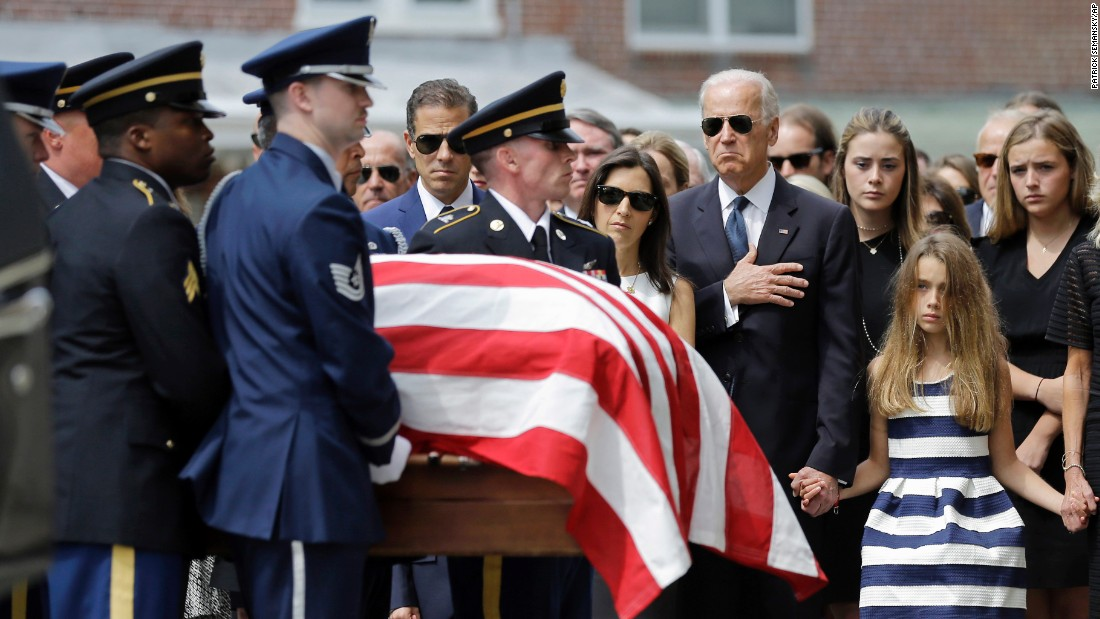 Vice President Joe Biden, accompanied by his family, holds his hand over his heart as he watches an honor guard carry a casket containing the remains of his son into St. Anthony of Padua Roman Catholic Church in Wilmington, on June 6. Standing alongside the vice president are Beau Biden's widow Hallie Biden, left, and daughter, Natalie.