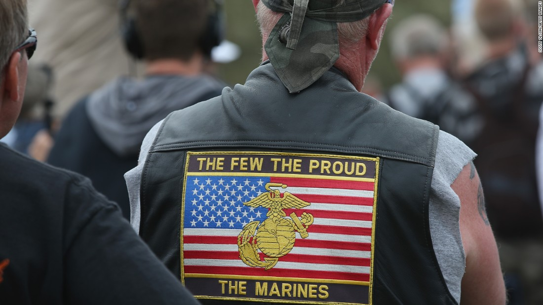 A spectator wearing a motorcycle vest emblazoned with a Marine patch listens to the speeches.