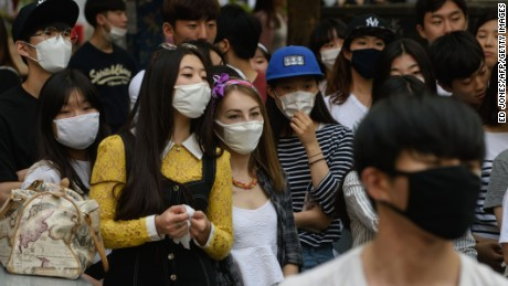 People wearing face masks watch a K-Pop performance on a street in the popular student area of Hongdae in Seoul on June 7. South Korea reported its fifth death from MERS as the government on June 7 vowed 'all-out' measures to curb the outbreak that was threatening to spread nationwide, including tracking mobile phones of those in quarantine.