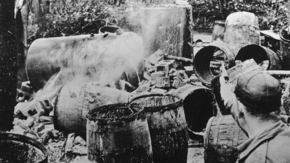 """Revenuers"" from the alcohol authorities shooting barrels after a raid to prevent their re-use in 1950."