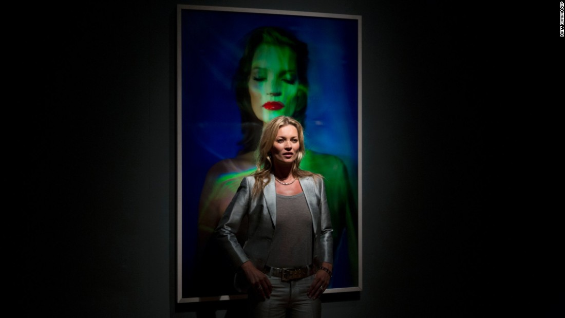 "Moss has inspired the creativity of many artists. Here, she poses beside ""She's Light (Laser 3)"" by Chris Levine at Christie's Auction House in London in September 2013."