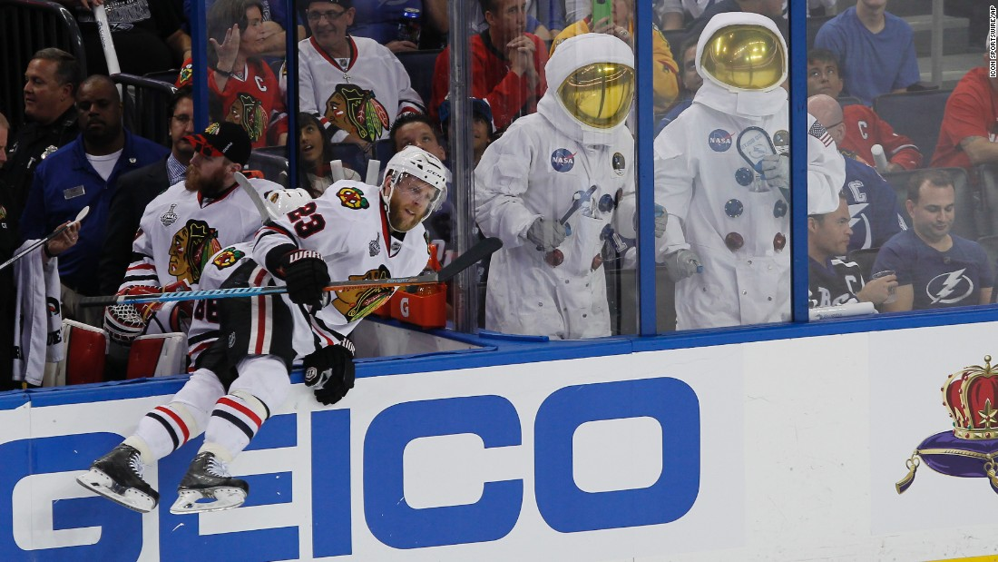 Chicago's Kris Versteeg jumps onto the ice Saturday, June 6, near two Tampa Bay Lightning fans dressed as astronauts. Chicago and Tampa Bay split the first two games of the Stanley Cup Final.