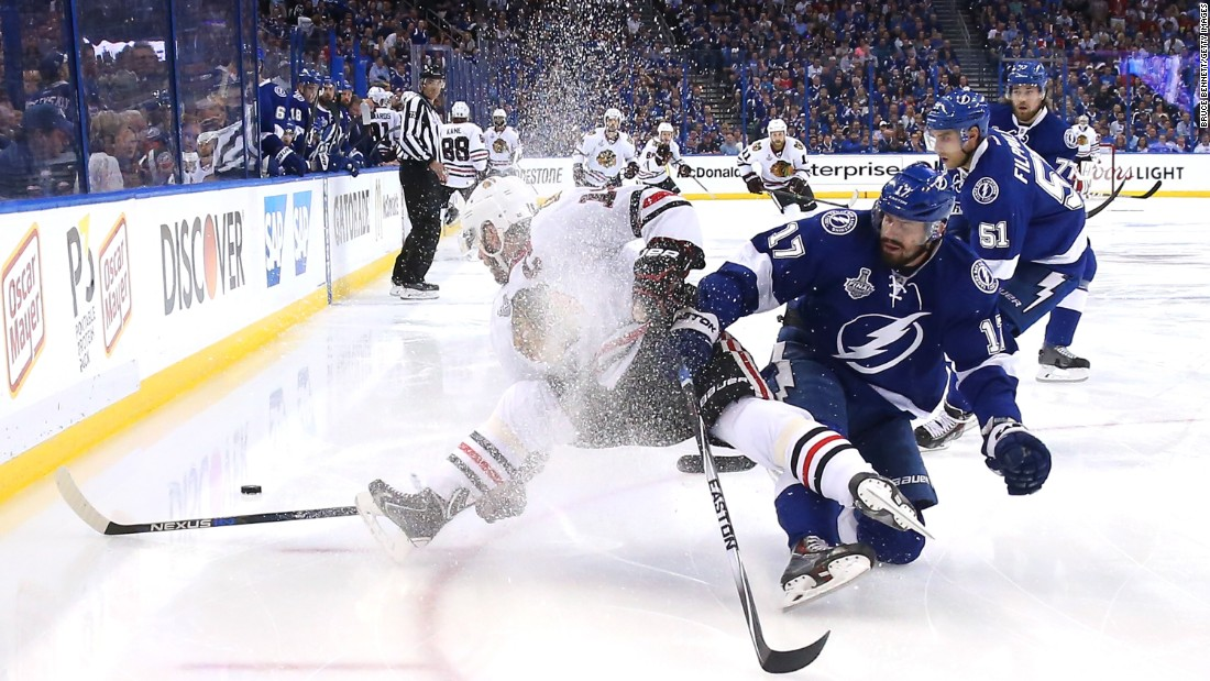 Ice sprays into the air as Tampa Bay's Alex Killorn, right, collides with Chicago's Jonathan Toews during Game 1 of the Stanley Cup Final on Wednesday, June 3.
