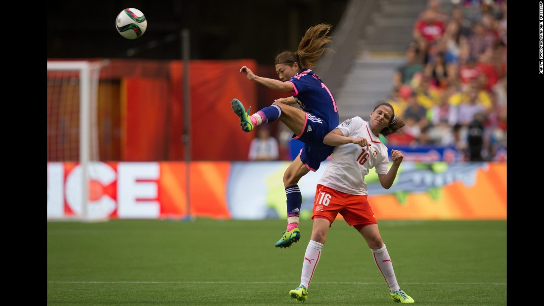 Japan's Rumi Utsugi kicks the ball out of the air as she jumps above Switzerland's Fabienne Humm.